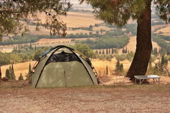 Barraca de camping no meio do terreno, debaixo de uma árvore Blog Vem Por Aqui