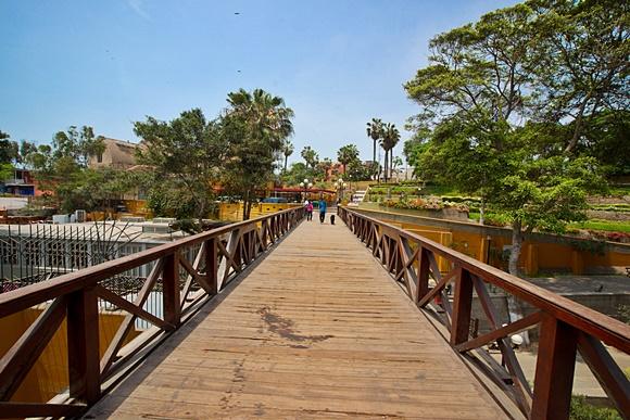 Ponte de madeira com árvores e parque ao fundo Blog Vem Por Aqui