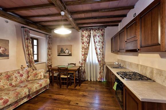 Sala com sofá e cortinas de estampa flora, mesa com quatro cadeiras no canto e bancada na parede em frente ao sofá com fogão e armários de cozinhas blog Vem Por Aqui