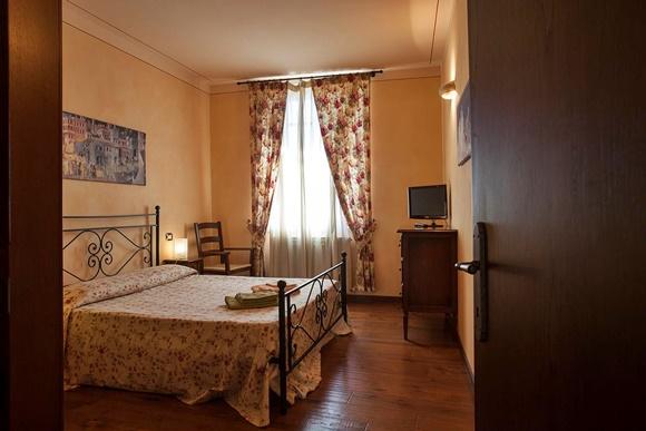 Porta aberta mostrando o quarto com cortina florida, cama grande e móvel com TV Blog Vem Por Aqui
