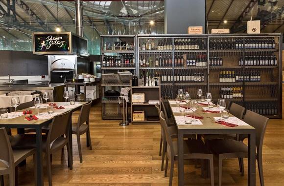 Mesas em frente à estante de vinhos na parte de cima do restaurante Blog Vem Por Aqui