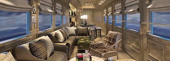 Interior do trem com poltronas diante das janelas, mesas e cadeiras cobertas com mantas de trama típica Blog Vem Por Aqui