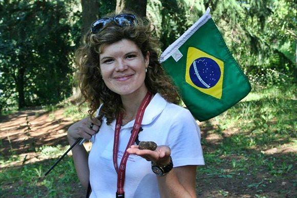 Deyse com uma bandeirinha do Brasil na mão direita e uma trufa na esquerda Blog Vem Por Aqui