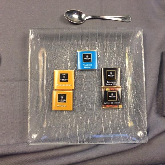 Pratinho de vidro com cinco chocolates pequenos e uma colher pequena em cima Blog Vem Por Aqui