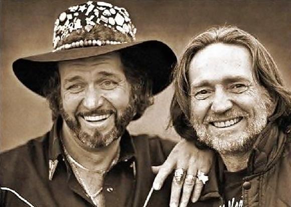 Foto em preto e branco dos dois artistas sorrindo, Waylon à esquerda, de chapéu, e Willie, à direita, de cabelo comprido Blog Vem Por Aqui
