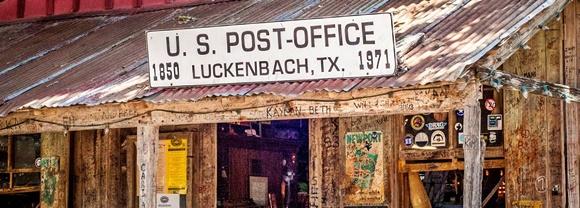 Placa em cima do prédio onde está escrito US Post-Office e, abaixo, a data 1850 Luckenbach, TX. 1971 Blog Vem Por Aqui