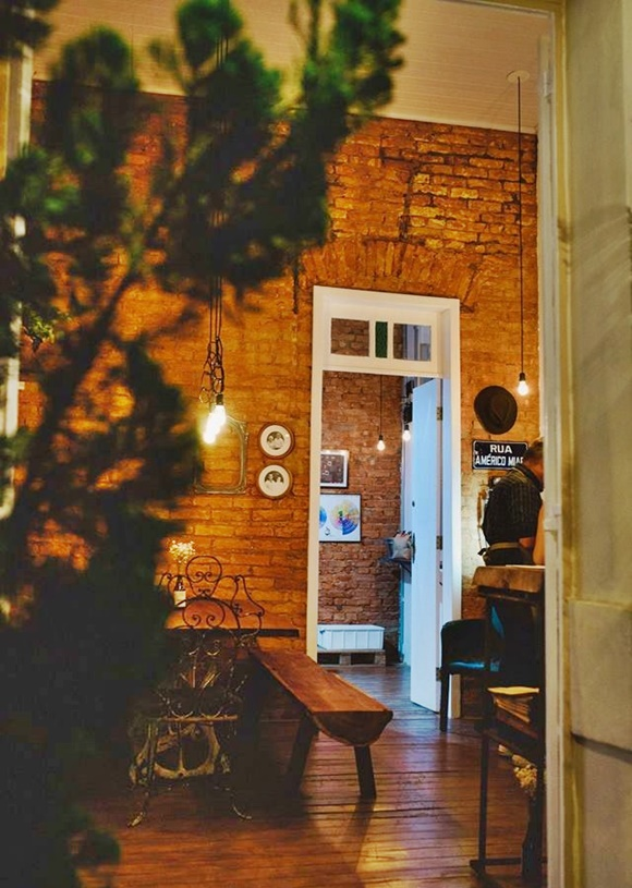 Sala de entrada no Café Américo com parede de tijolos Blog Vem Por Aqui