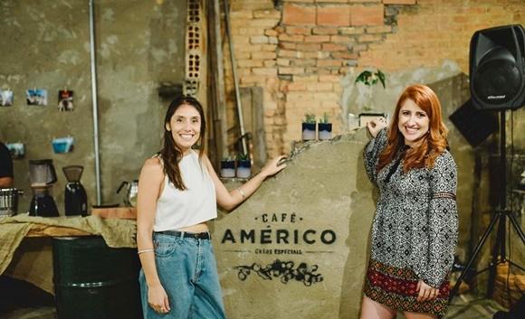 Juliana Miari, do Café Américo e Érika Gimenes em volta de uma parede com a marca Café Américo Blog Vem Por Aqui