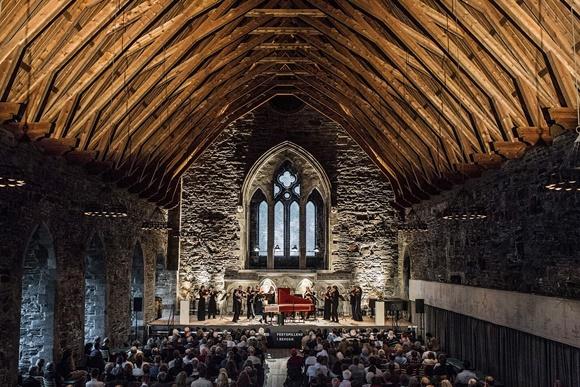 Orquestra se apresentando dentro de uma igreja com teto alto de madeira e público assistindo sentado Blog Vem Por Aqui