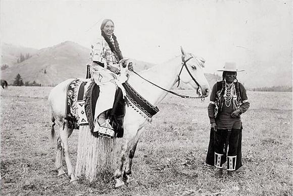 Índia montada num cavalo banco sorrindo e outra, de chapéu, em pé, na frente Blog Vem Por Aqui