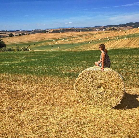 Deyse sentada num monte redondo de feno no meio de um campo com ovelhas ao fundo Blog Vem Por Aqui