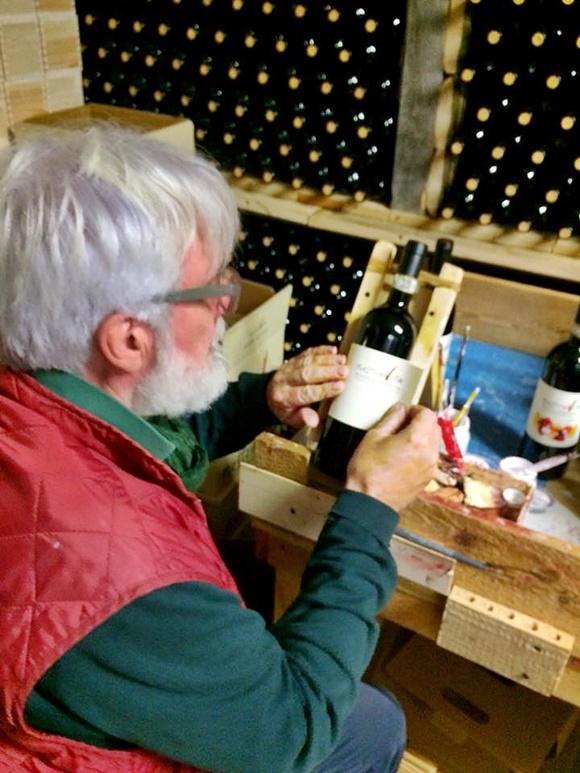 Produtor de vinho colando rótulo à mão em garrafa de vinho Blog Vem Por Aqui