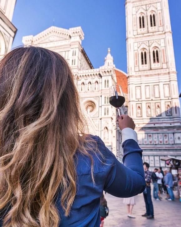 Deyse de costas para uma igreja com uma taça de vinho levantada Blog Vem Por Aqui