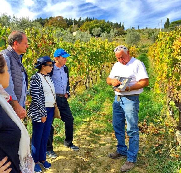 Produtor dando explicações para um grupo de quatro turistas no meio de um vinhedo Blog Vem Por Aqui