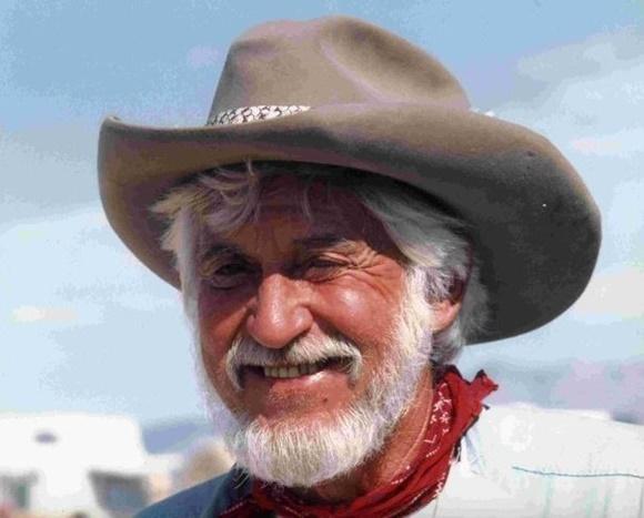 Hondo sorrindo, de chapéu country, barba e cabelo brancos, lenço vermelho no pescoço e camisa jeans Blog Vem Por Aqui
