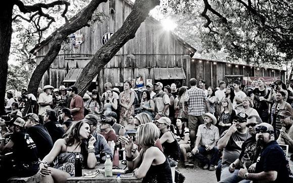 Pessoas espalhadas pelas mesas do lado de fora do saloon Blog Vem Por Aqui