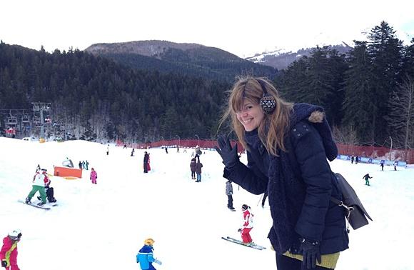 Deyse na lateral de uma pista, com roupa de inverno, sorrindo e acenando Blog Vem Por Aqui