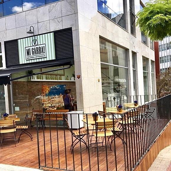 Loja da Mi Garba vista de fora com mesinhas no deck e placa na fachada Blog Vem Por Aqui