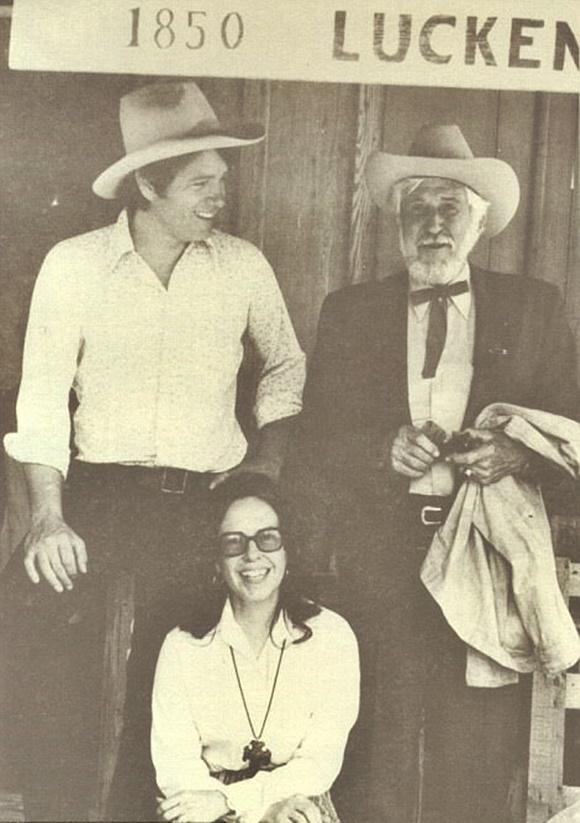 Foto com o trio, homens em pé e mulher sentada no meio, abaixo de uma placa com a data 1850 e a palavra Luckenbach Blog Vem Por Aqui