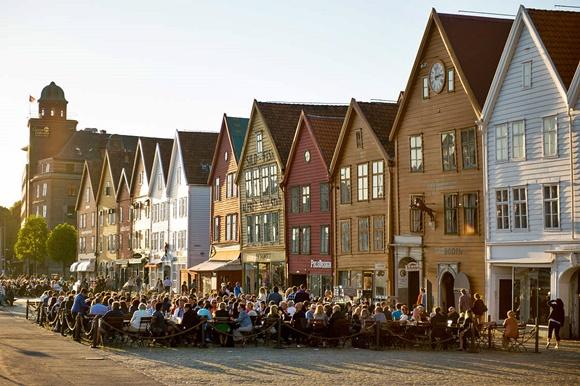 Pessoas sentadas em mesas de bares diante dos prédios coloridos Blog Vem Por Aqui