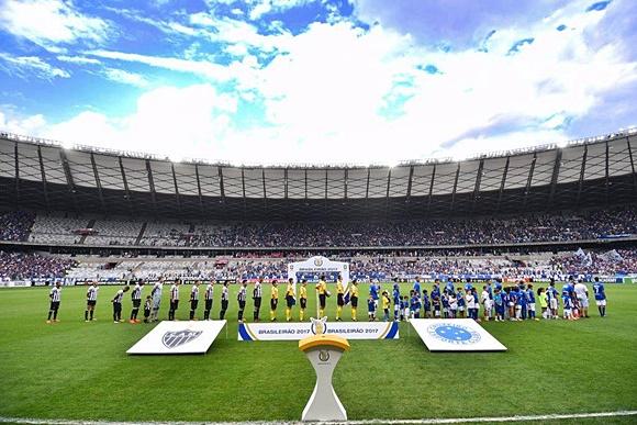 Jogo entre Atlético e Cruzeiro no Mineirão com taça diante do escudo dos dois clubes e times atrás Blog Vem Por Aqui