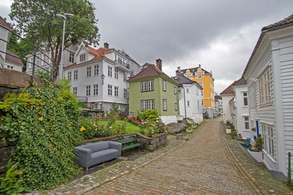 Casas de madeira em ruazinha de pedra com sofá ao lado de um banco de madeira no começo da rua Blog Vem Por Aqui