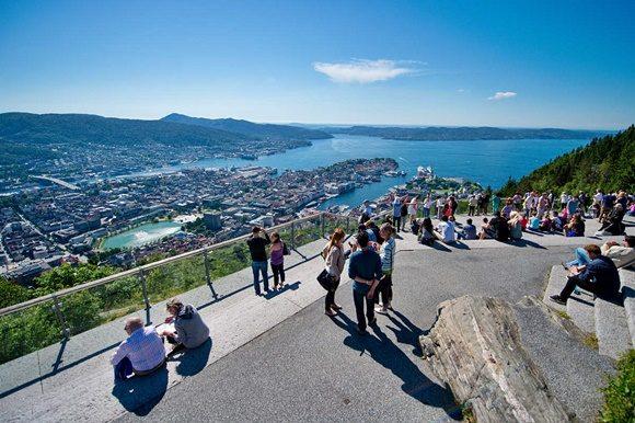 Pessoas no topo da montanha observando a vista que dá para o mar e as casas da cidade Blog Vem Por Aqui