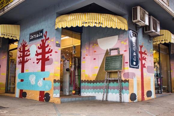 Fachada da loja com pintura toda colorida e toldo listrado de amarelo e branco com o nome Blog Vem Por Aqui
