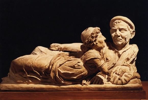 Estátuas de uma homem deitado de lado e mulher de frente para ele na tampa de uma urna Blog Vem Por Aqui