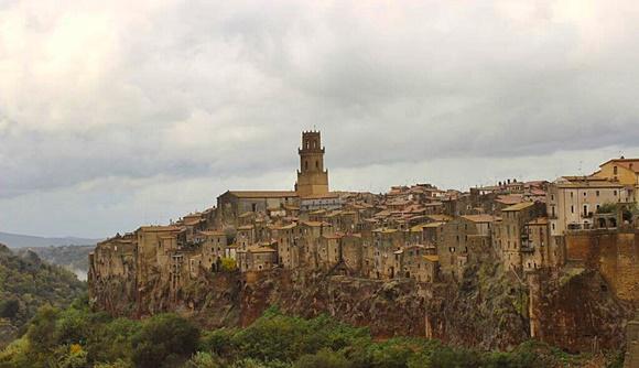 Cidade vista do alto com torre no meio e rocha vermelha abaixo das construções Blog Vem Por Aqui