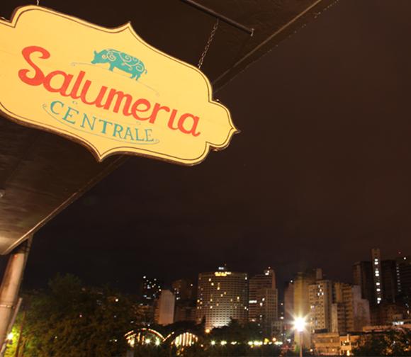 Placa da Salumeria vista de baixo com céu escuro, de noite, acima e prédios da cidade ao fundo Blog Vem Por Aqui