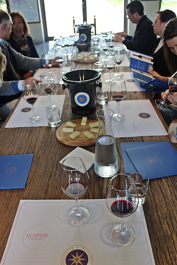Mesa com pessoas degustando os vinhos da Tenuta, com taças, água e bandeja de queijos Blog Vem Por Aqui