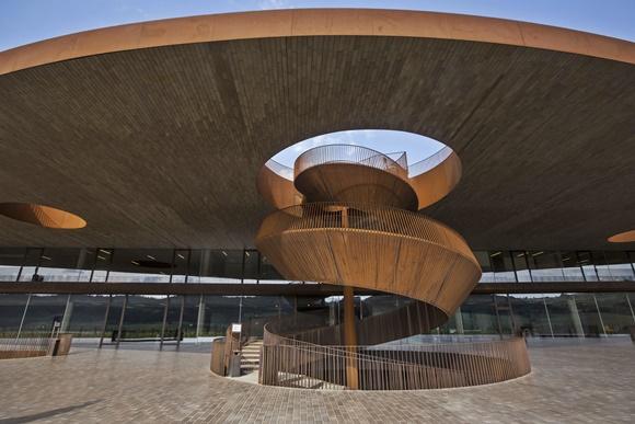 Escada em espiral no meio da vinícola, que sobe para o teto arredondado Blog Vem Por Aqui
