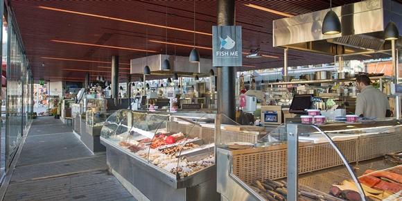 """Bancas do mercado com peixes e placa com a inscrição """"Fish Me"""" pregada numa coluna no meio de uma das bancas Blog Vem Por Aqui"""