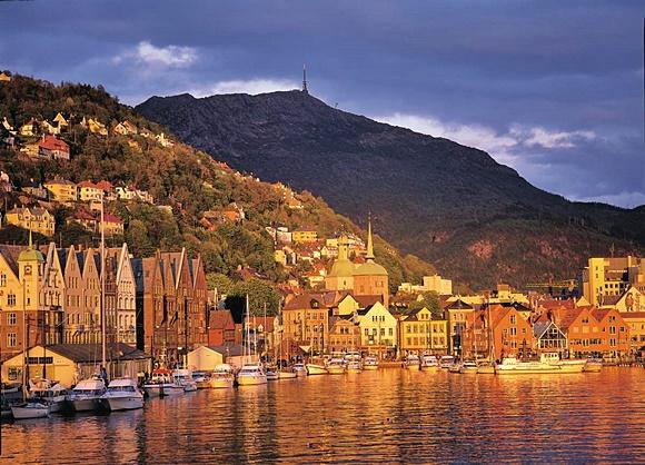 Rio com prédios de madeira coloridos nas margens, barcos atracados e montanha ao fundo Blog Vem Por Aqui