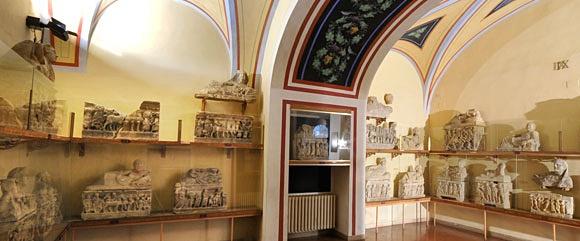 Cômodo do museu com várias urnas em formato de caixa pequenas com tampas decoradas em alabastro Blog Vem Por Aqui