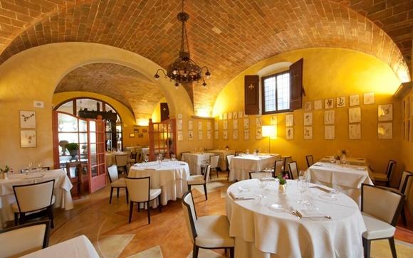 Salão do restaurante com mesas com cadeiras branca de moldura preta e toalhas longas brancas, teto antigo de tijolos e janela no alto Blog Vem Por Aqui