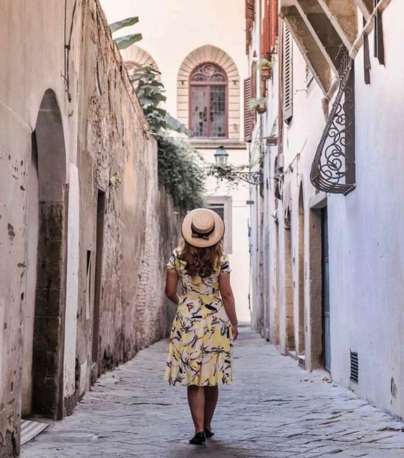 Deyse caminhando numa rua estreita numa cidadezinha da Toscana, de costas para a câmera, de vestido flora e chapéu Blog Vem Por Aqui