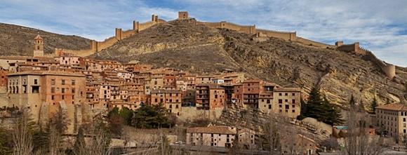 Vista panorâmica de Albarracín com casas em tons de terra e muralha no alto da montanha Blog Vem Por Aqui