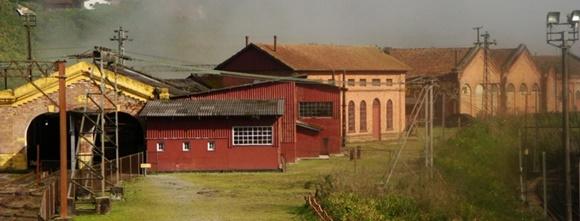 Casas vermelhas ao lado de casas maiores em tons de terra com a linha do trem passando atrás Blog Vem Por Aqui