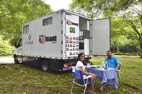 Glória e Renato sentados em numa mesinha em frente ao caminhão parado num parque com a porta de trás aberta, de onde é possível ver o fogão Blog Vem Por Aqui