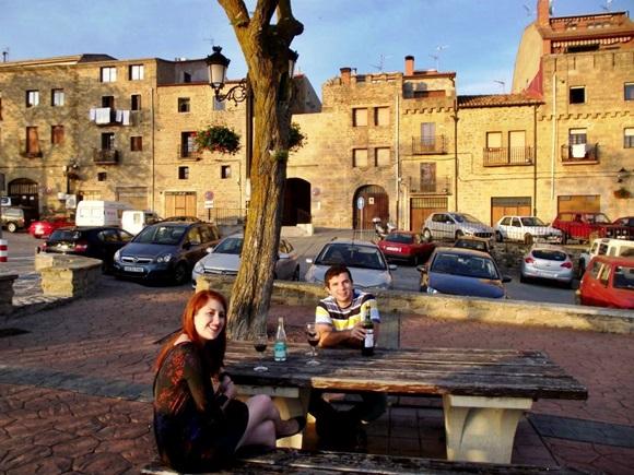Érika e o irmão, Igor, sentados em bancos de madeira, uma de frente para o outro, com uma mesa de madeira no meio e casas mediavais atrás com vários carros parados em frente Blog Vem Por Aqui