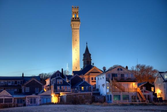 Casas pequenas com uma torre alta e iluminada atrás Blog Vem Por Aqui