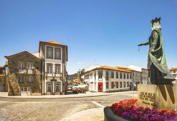 Estátua vista de costas do outro lado da rua, diante de prédios da cidade, uma casa de pedra, uma casa de três andares com janelas largas e uma casa baixa de dois andares Blog Vem Por Aqui
