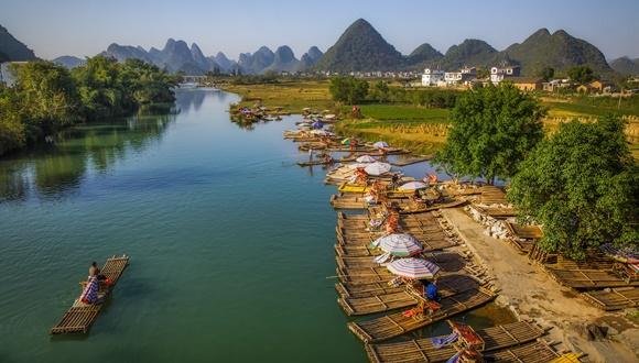 Rio com jangadas de bambu na margem de uma delas passando no meio Blog Vem Por Aqui