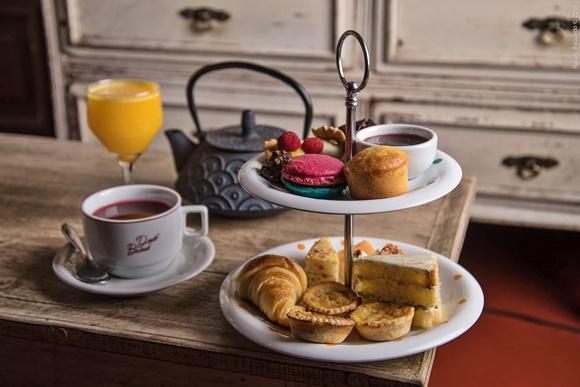 Combo de lanche da tarde com chocolate quente, suco de laranja e bandeja de dois andares com macaron, bolo, calda e, embaixo, croissant, quiches e torta Blog Vem Por Aqui