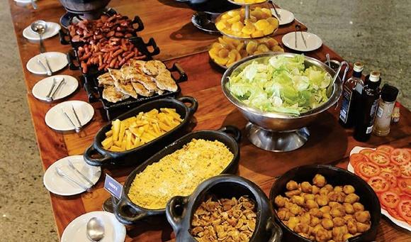 Buffet com itens da feijoada e outras coisas como filé de frango, batata frita e farofa. Tudo em chapas de ferro ou panelas de barro, em cima de uma grande mesa de madeira Blog Vem Por Aqui