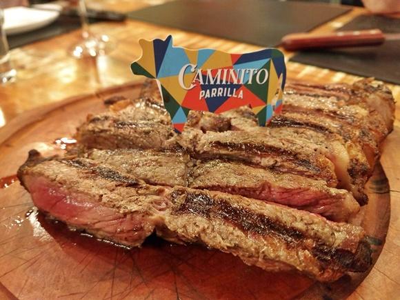 Porção de bife de chorizo do Caminuto numa tábua de madeira com uma placa de vaquinha colorida com o nome da casa em cima Blog Vem Por Aqui