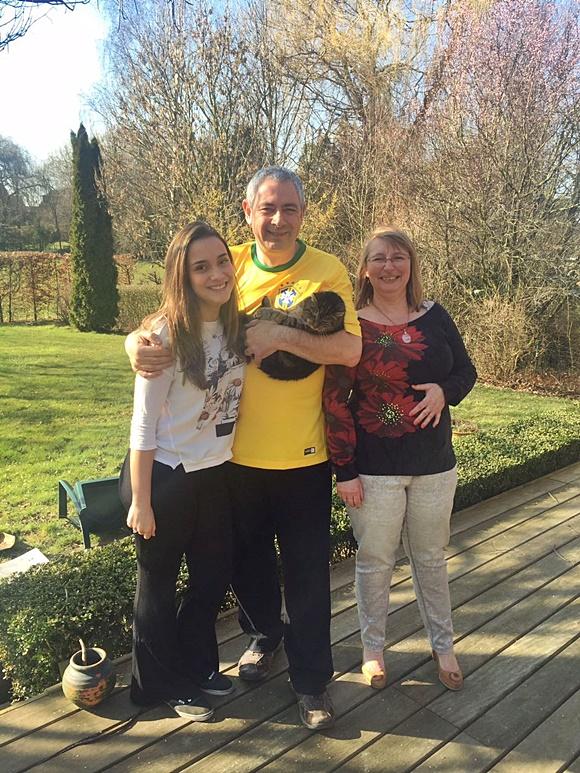 Clara abraçada ao pai belga, que segura uma gata no outro braço e está do lado da mãe belga. Blog Vem Por Aqui