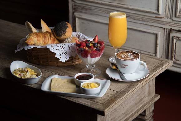 Combo de café em cima de mesa de madeira, cesta com pães, tigela com ovo mexido, bandeja com geleia, manteiga e queijo, taça com iogurte com frutas vermelhas, café e suco de laranja Blog Vem Por Aqui